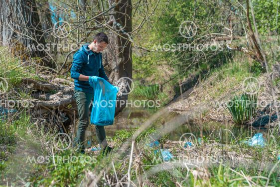 volunteer collects plastic waste on the river bank,...