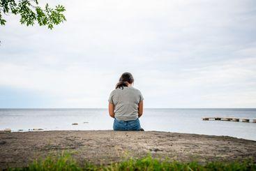 Ensam flicka sitter på klippa tittar på havet.