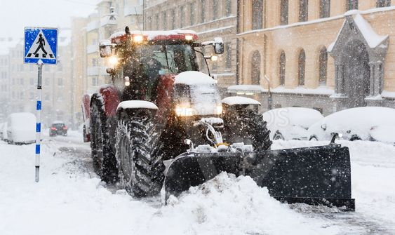 Plow removing snow from city street in Stockholm.