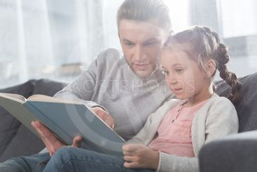 Father teaching daughter read at home