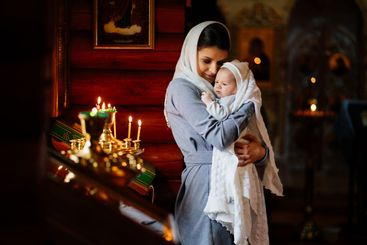 beautiful mom in a headscarf with a small child in her...