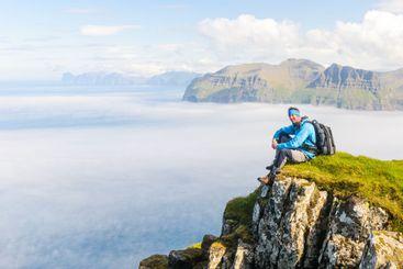 Hiker sitting with a view. Mykines, Faroe Islands