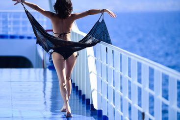 Sexy woman walk on deck of cruise liner with sea on...