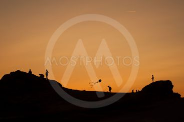 children silhouettes with kite flying on sunset...