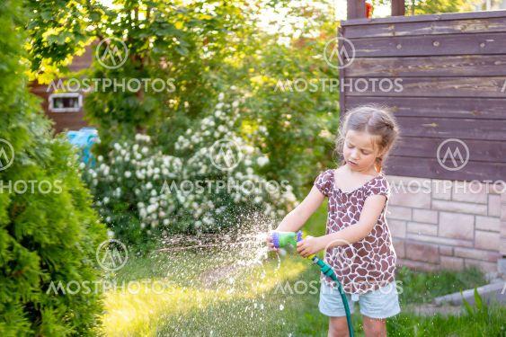 Portrait of little gardener girl, she is watering...