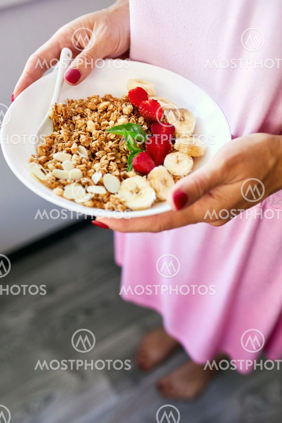 Woman eating healthy breakfast bowl, hold in hand