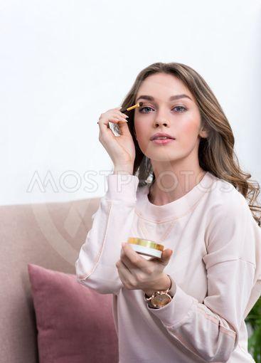 beautiful young woman applying makeup and looking at...