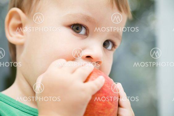Portrait of a cute little boy biting apple