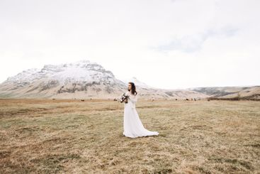 Portrait of a bride in a white wedding dress, with a...