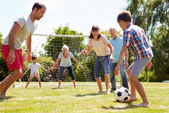 Multi Generation Playing Football In Garden Together