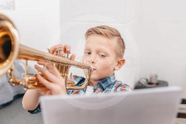 boy practicing trumpet