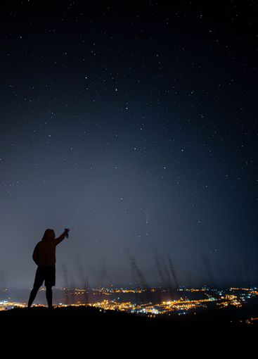 una  persona apuntando al cometa neowisse