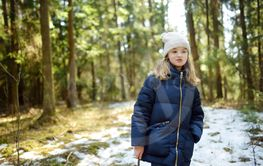 Cute young girl having fun during forest hike on...