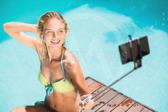 Beautiful woman in bikini taking a selfie by pool side