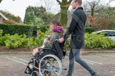 Man pushing a woman in a wheelchair at a car park