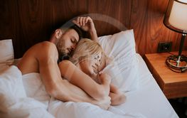 Lovely couple hugging on their bed at home