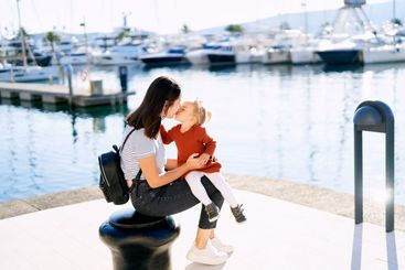 Mother is kissing her baby girl while sitting on a pier...