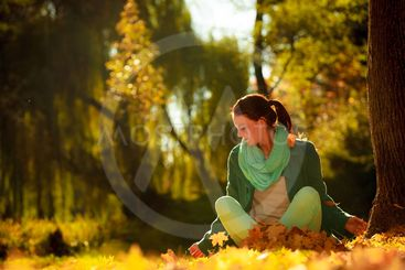 girl relaxing in colorful forest foliage outdoor.