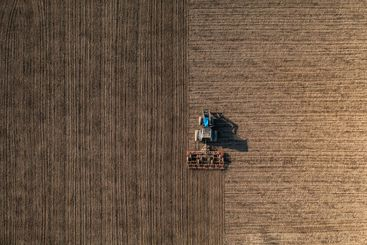 Top view of a tractor harrowing soil.