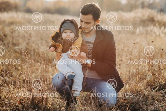 young dad with son boy child sitting in nature in autumn
