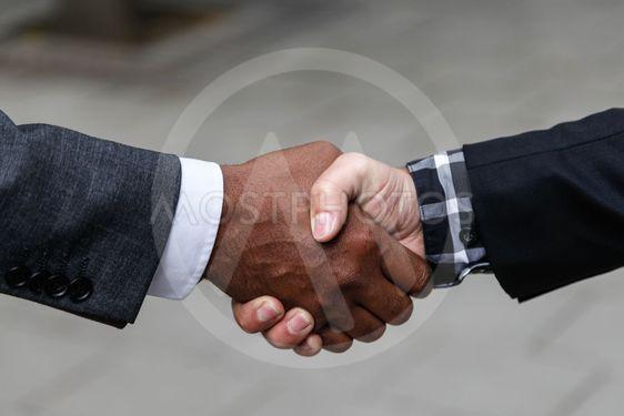Handslag mellan svart och vit man