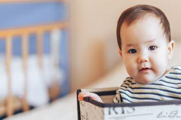 pretty baby infant boy or girl sitting inside a box in...