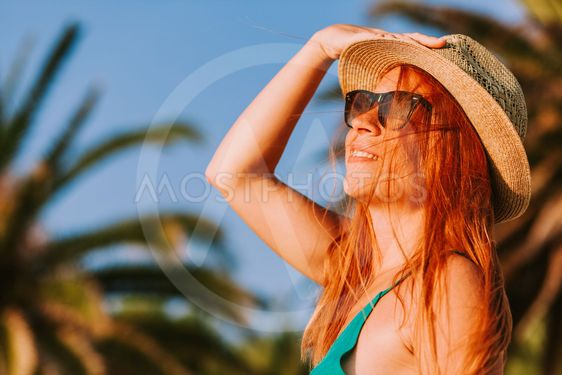 Young woman enjoying the view by the palm trees