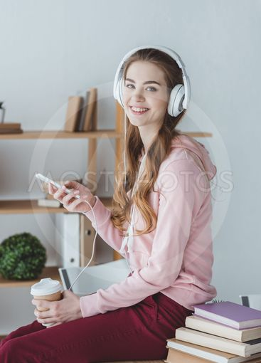 smiling blonde student with coffee listening music with...