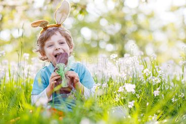 Little toddler wearing Easter bunny ears and eating...