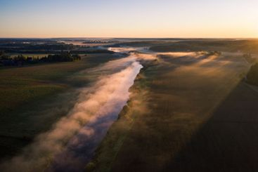 Aerial view of fog above a river valley at dawn
