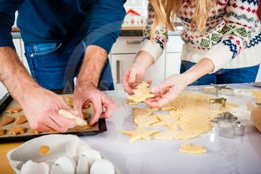 Couple baking Christmas cookies in kitchen