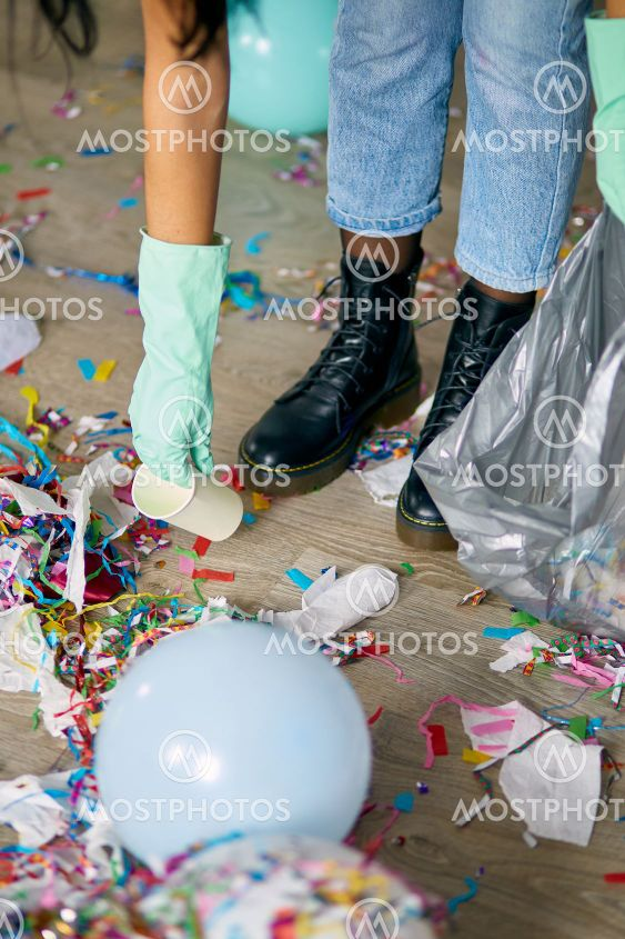 Woman with pushbroom cleaning mess of floor in room
