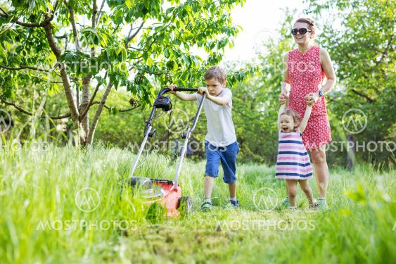 Young boy mowing grass with lawn mower, mother and...