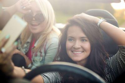 Girlfriends taking selfie in car