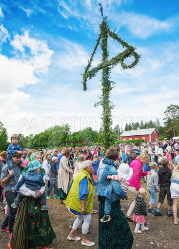 Traditional swedish midsummer with people dancing around...