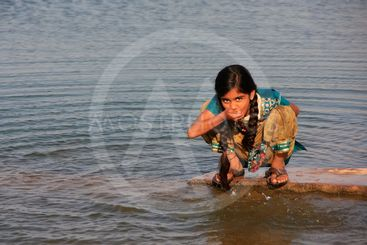 Local girl drinking from water reservoir, Khichan...