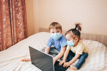 Two children brother and sister in medical masks using...