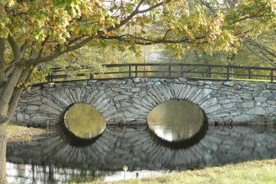 Stone arch bridge over glassy water