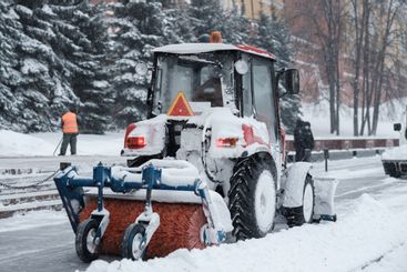 A small tractor sweeps snow from the sidewalk near the...