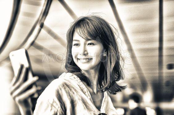 Beautiful japanese woman looking at smartphone inside...