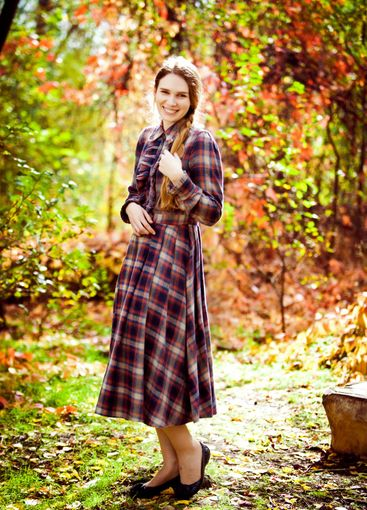 woman in plaid dress in autumn forest. nature walks.