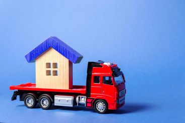Red truck carrier transports a blue roofed house....