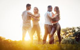 Two couples dancing kizomba during sunset in a park