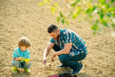 Happy young father planting a tree while his little son...