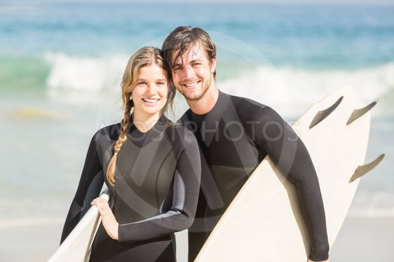 Portrait of couple with surfboard standing on the beach