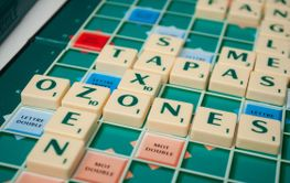 crosswords with plastic letters on Scrabble board game
