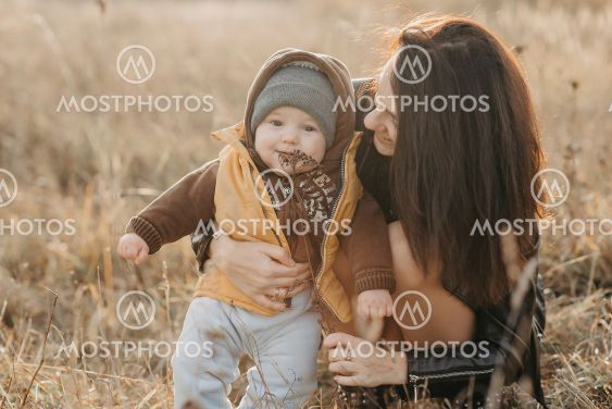 young mom playing with her little baby boy son in autumn