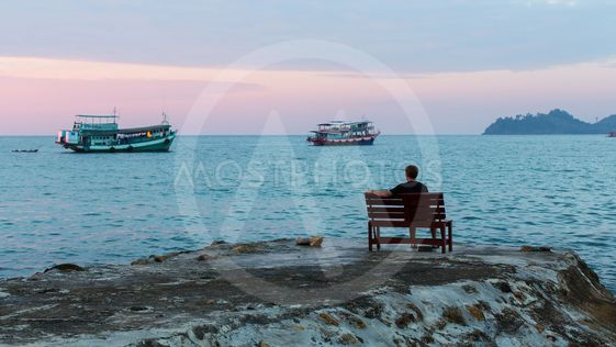 Lonely man on the evening shore of the sea.