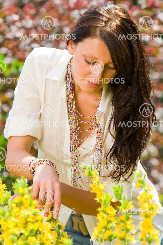 Kaunis nainen aurinkoinen puutarhan hoito keltainen kukat