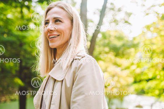 Caucasian blonde woman smiling happily on sunny summer...